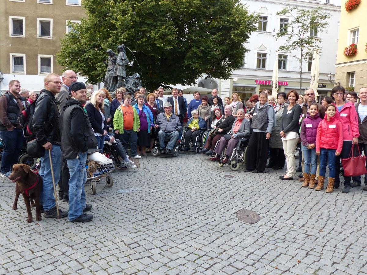 Die Teilnehmer am Wundernetz-Aktionstag stehen im Halbkreis zusammen auf dem Amberger Marktplatz