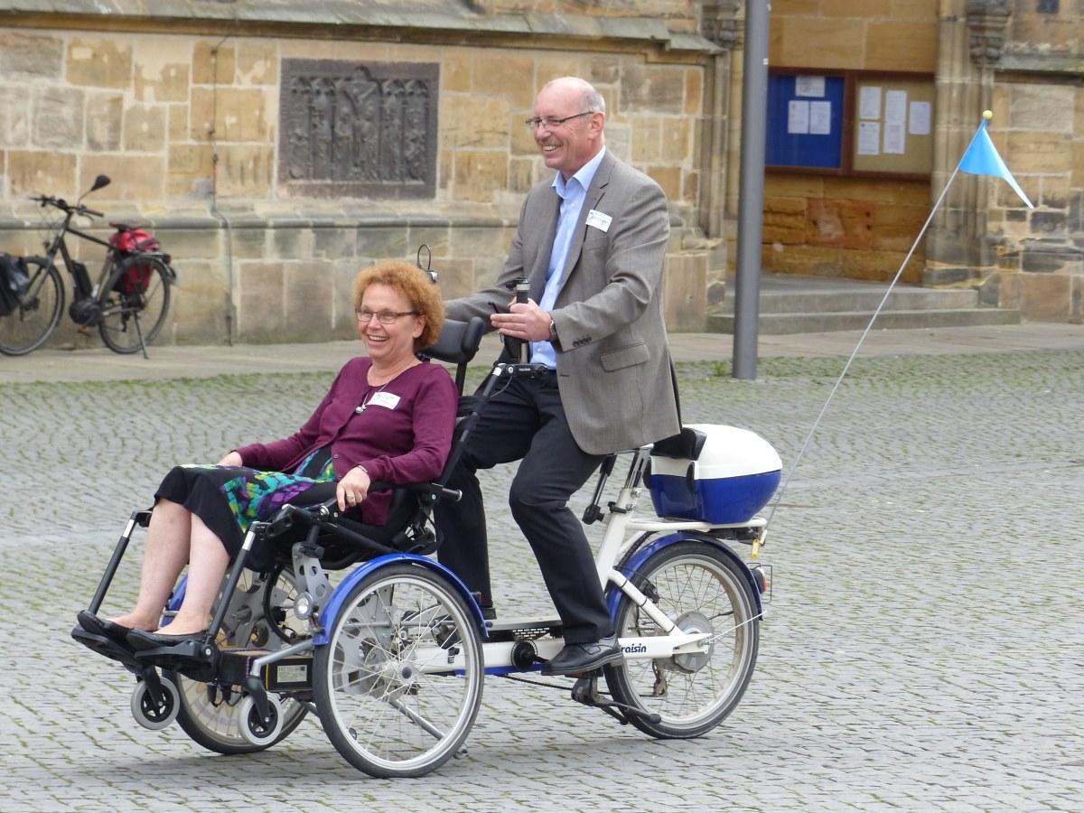 Zwei Besucher testen das Rollstuhlfahrrad