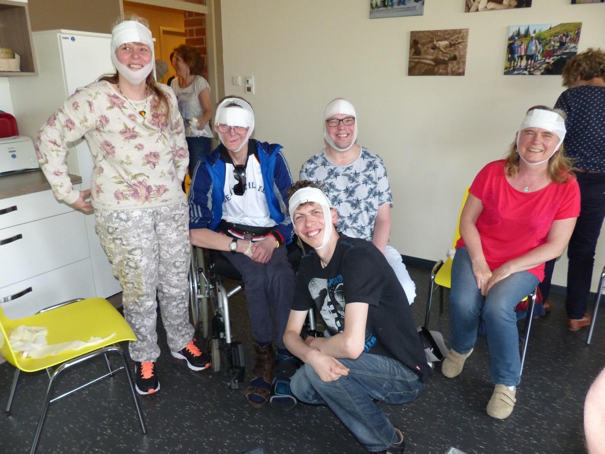 Gruppenbild von lachenden Kurs·teilnehmern mit Kopf·verband