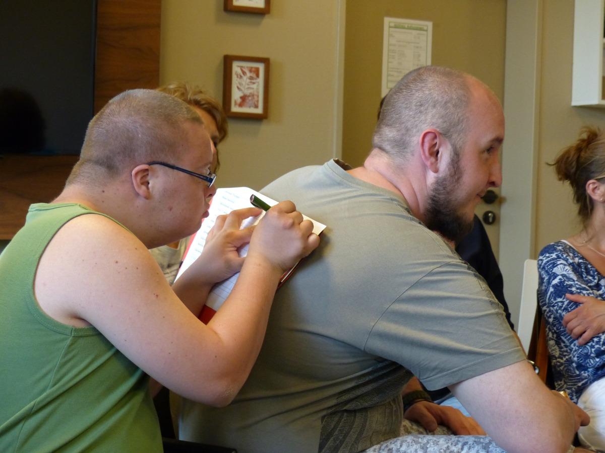 Teilnehmer benutzt Rücken als Schreib·unterlage