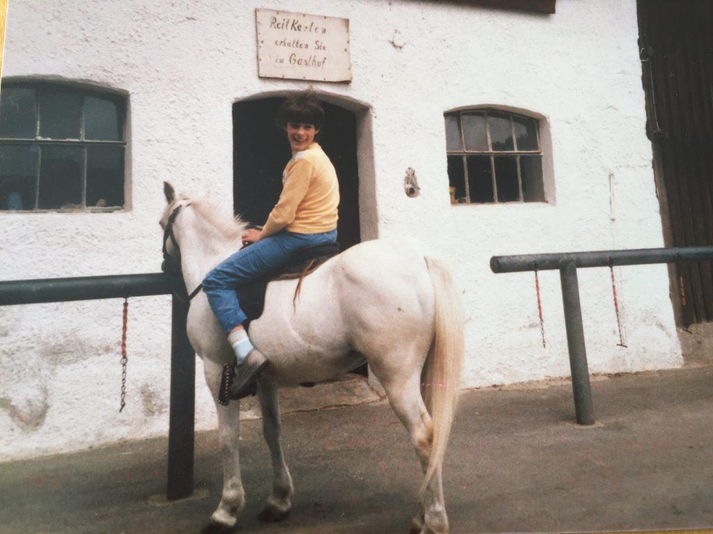 Carola sitzt auf einem weissen Pferd. Sie steht mit dem Pferd vor dem Stall.