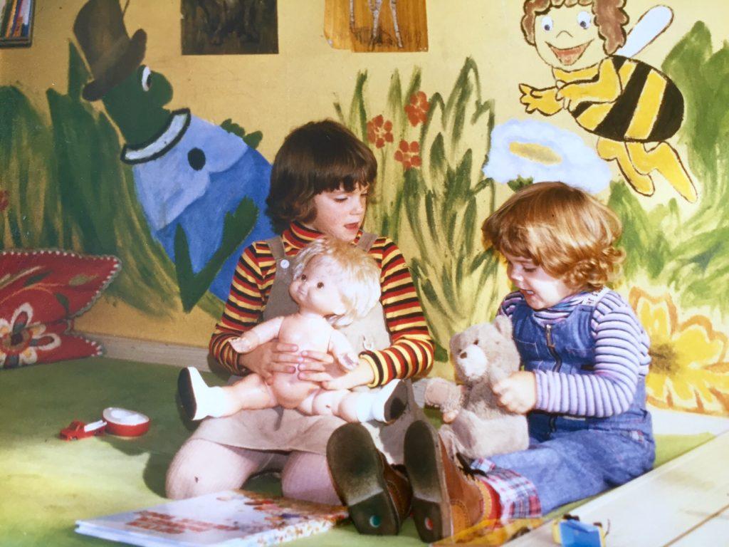 Carola und ihre Schwester Sonja als kleine Mädchen. Sie sitzen auf dem Boden und spielen mit einer Puppe und einem Teddynbären.