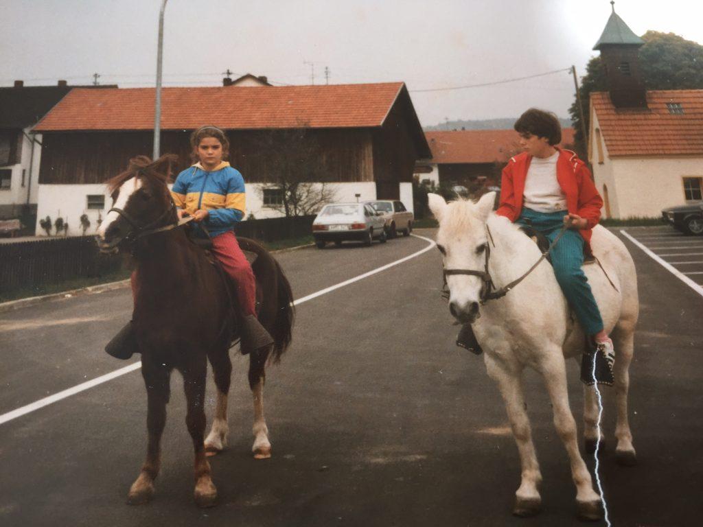 Carola und ihre Schwester Sonja sitzen auf Pferden. Sie reiten auf einer Strasse.