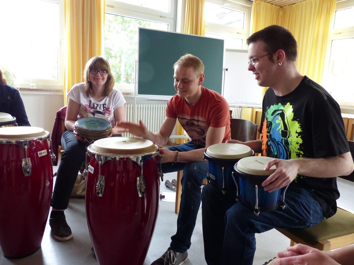 Drei Kursteilnehmer spielen auf verschiedenen Trommeln