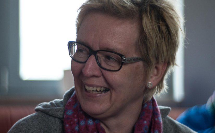 Eine lachende Frau bei einer Redaktionssitzung