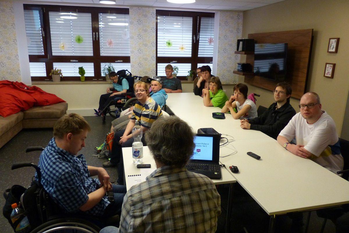Die Teilnehmer der Ausbildung sitzen an einem Tisch und hören dem Referenten zu