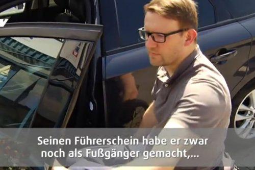 Jürgen im Rollstuhl vor seinem Auto.