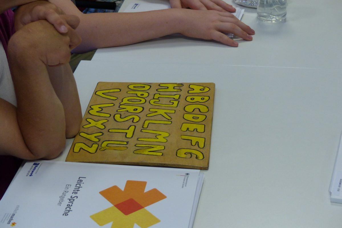Auf einem Tisch liegt ein Brett mit dem Alphabet in großen gelben Buchstaben