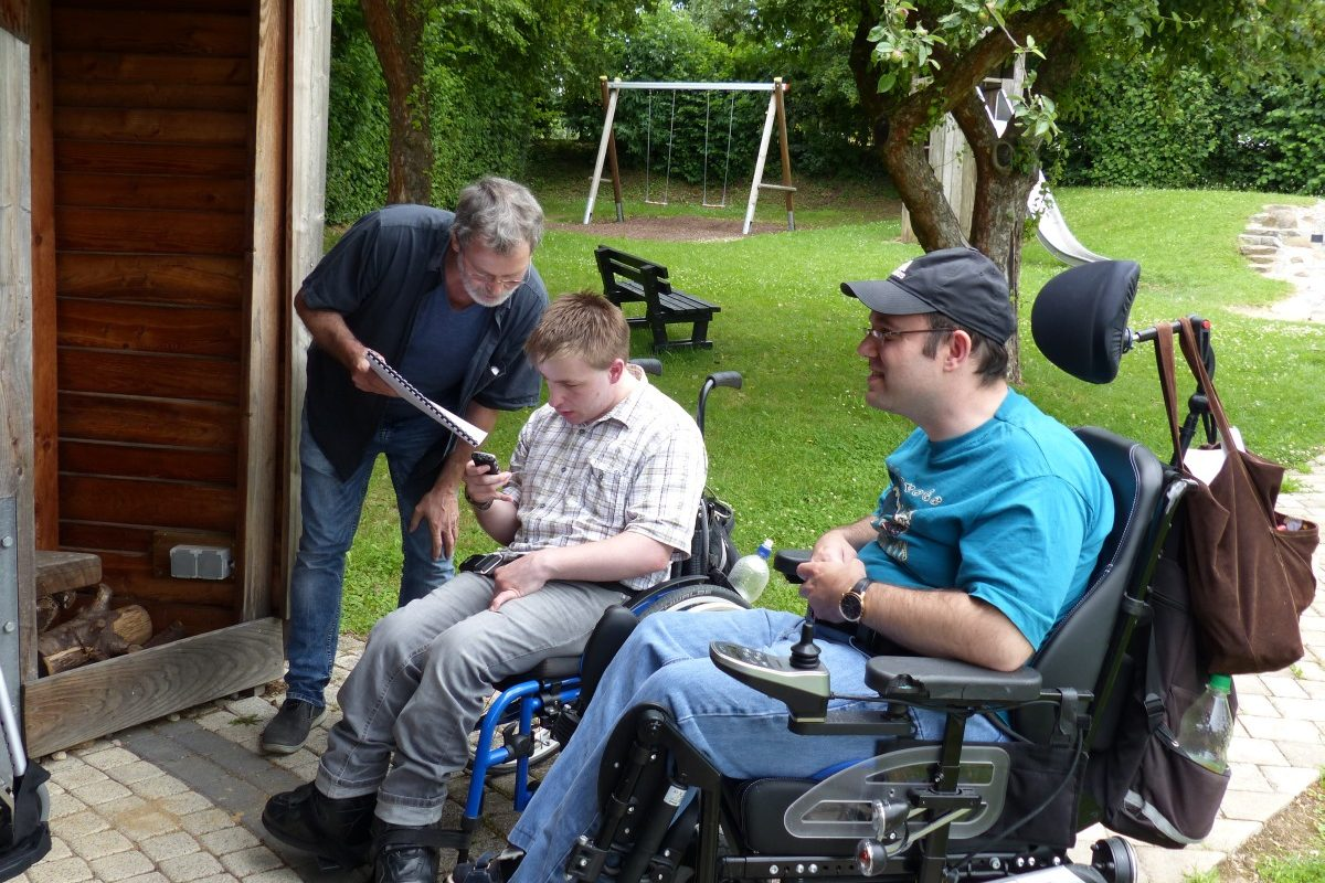 Zwei Rollstuhlfahrer im Gespräch mit einem Mann der ein Heft hält