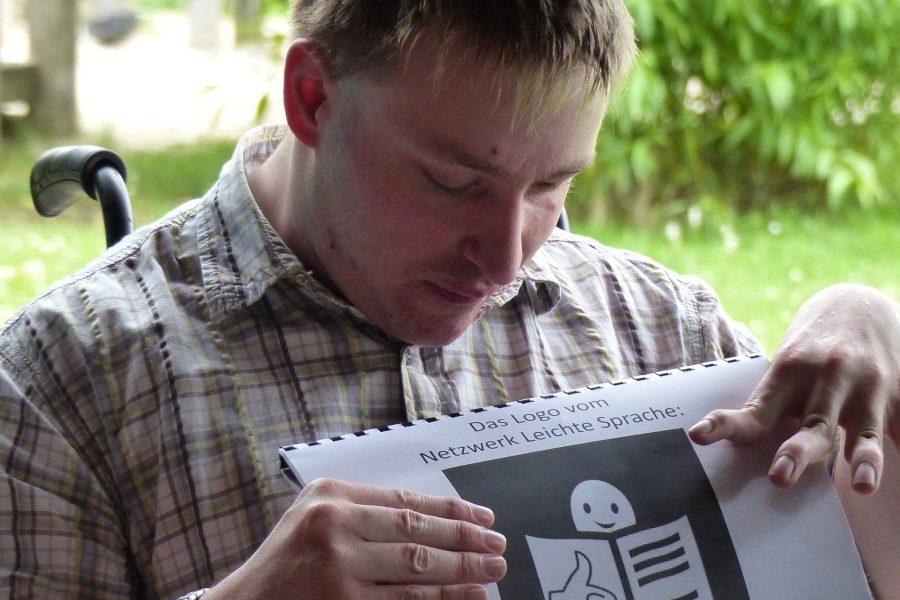 Ein junger Mann hält das Logo vom Netzwerk für Leichte Sprache in der Hand