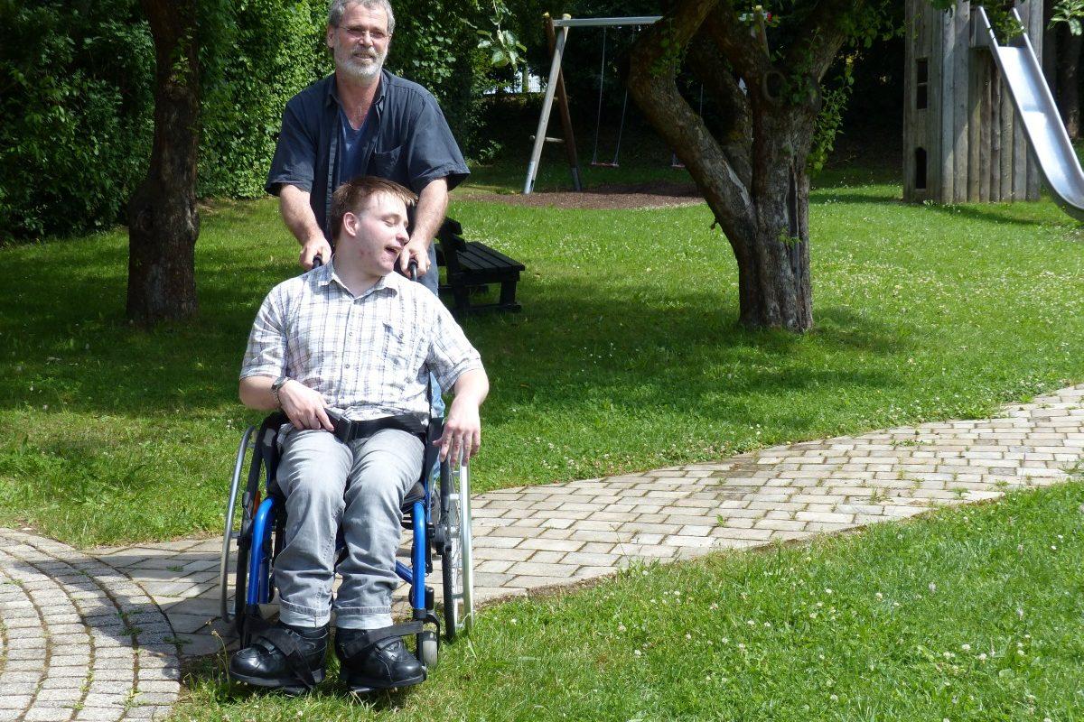 Ein Mann schiebt einen Rollstuhlfahrer über eine Rasenfläche