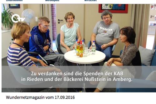 Hildegard und Werner sitzen mit Leuten an einem Tisch, die für das Wundernetz gespendet haben.