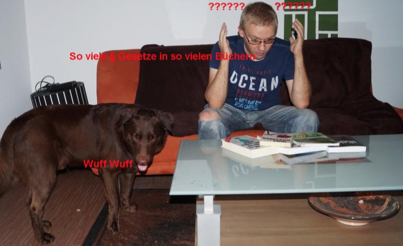 Andreas und Therapiehund Janosch vor einem Tisch auf dem Gesetzesbücher liegen. Andreas sieht verzweifelt aus.