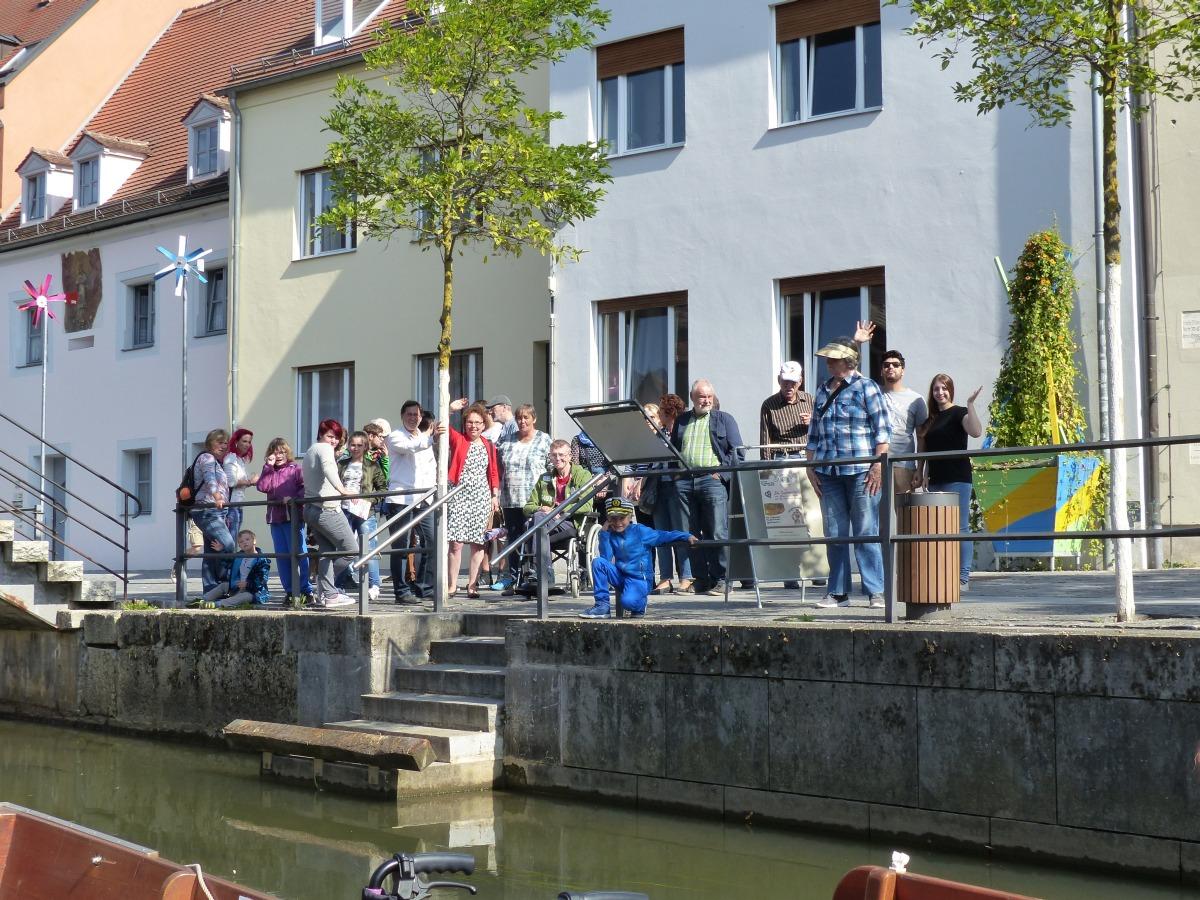 Menschen stehen am Ufer und warten auf die Plätte.