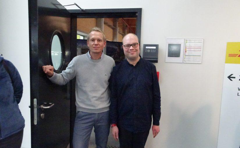 Oliver und ein Mitarbeiter der Schilderfabrik Moedel gehen durch eine Tür
