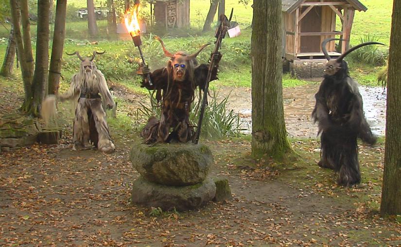 Drei Menschen mit Dämonenverkleidung stehen um einen Stein herum.