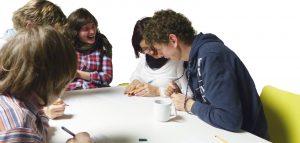 Mehrer Mitglieder des Wundernetz-Teams sitzen um einen Tisch und diskutieren. Ein Mädchen lacht.