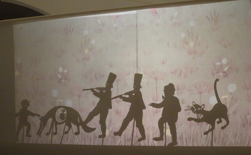 Im Schattenspiel sind die Umriss von Menschen und Tieren zu sehen.