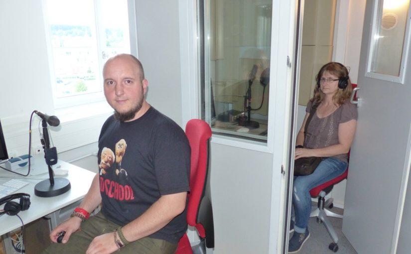 Eine Person sitzt in der Sprachkabine der OTH und liest einen Text ein. Eine zweite Person sitzt vor der Kabine und nimmt den Text auf.
