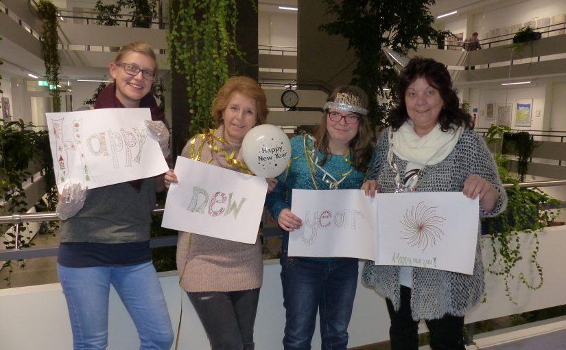 Vier Damen vom Wundernetz wünschen mit Zetteln ein frohes, neues Jahr