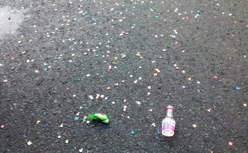 Eine kleine Schnapsflasche und Konfetti liegen auf der Straße