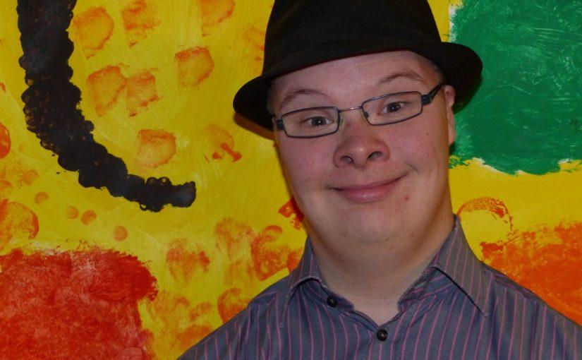 Torsten Lehmeier mit einem Hut vor einem bunten Hintergrund.