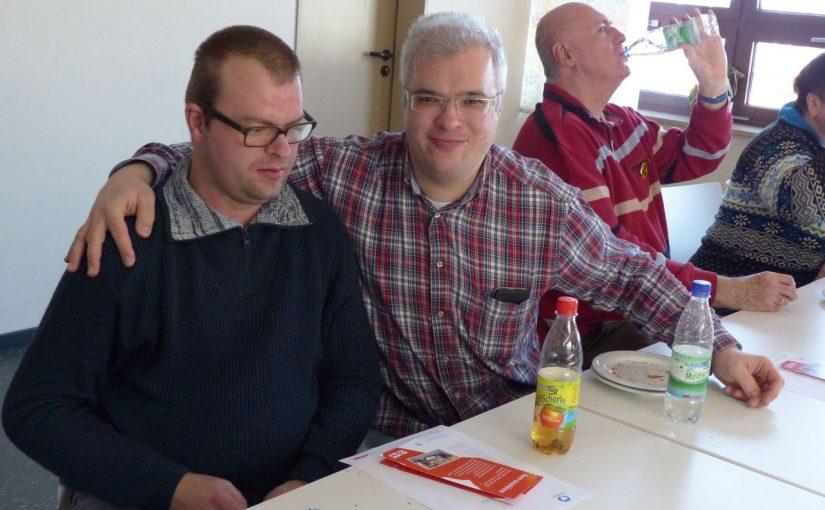 Daniel und Christof sitzen nebeneinander und lächeln in die Kamera