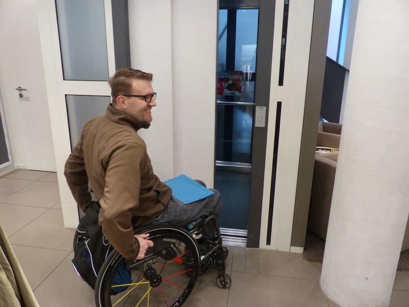 Ein Teilnehmer im Rollstuhl vor einer verschlossenen Aufzugtür
