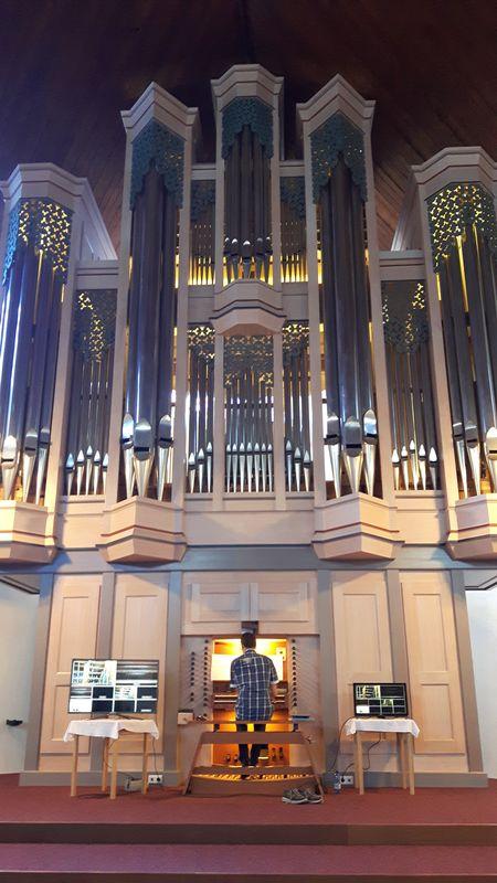 Herr Feyrer spielt an der Orgel. Er wirkt winzig vor dem riesigen Instrument.