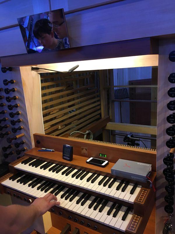Blick auf das Umfeld der Tastatur. Oberhalb sieht man in einem kleinen Spiegeln Herrn Feyrer und einen Schüler