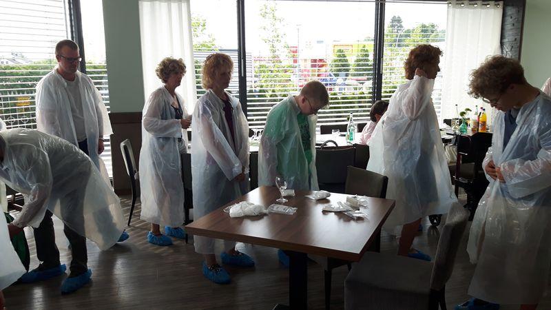 Vor der Führung ziehen alle Besucher Schutzmäntel aus dünnem, durchsichtigem Plastik an.