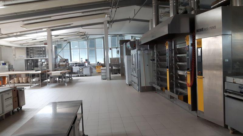 Blick in die große, leere Produktionshalle der Bäckerei. Man sieht viele Regale und Öfen.