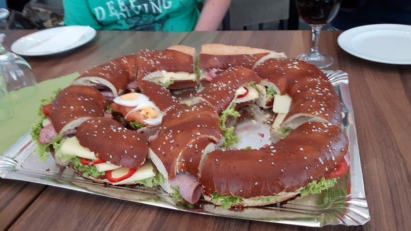 Eine riesige Breze ist belegt mit Käse, Schinken, Salat und Eiern. Sie ist in handliche Stücke geschnitten.