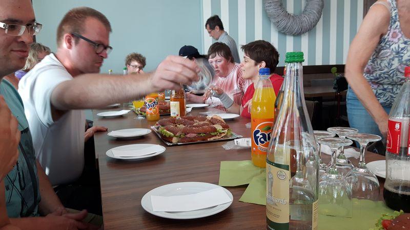 Nach der Führung gibt es eine leckere Brotzeit. Alle sitzen am Tisch.