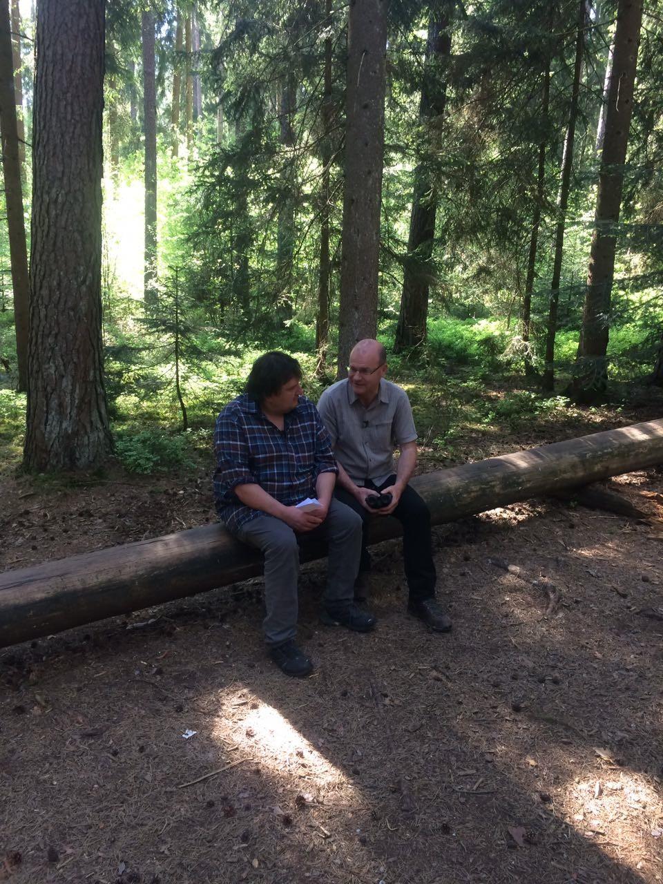 Robert und Norbert Schäffer vom LBV sitzen auf einem Baumstamm und unterhalten sich
