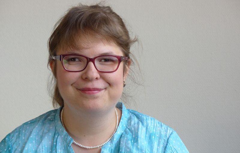 Porträt von Franziska Lottner. Sie trägt eine blau Bluse und eine Kette mit weißen Perlen. Sie hat braune Haare und eine Brille.