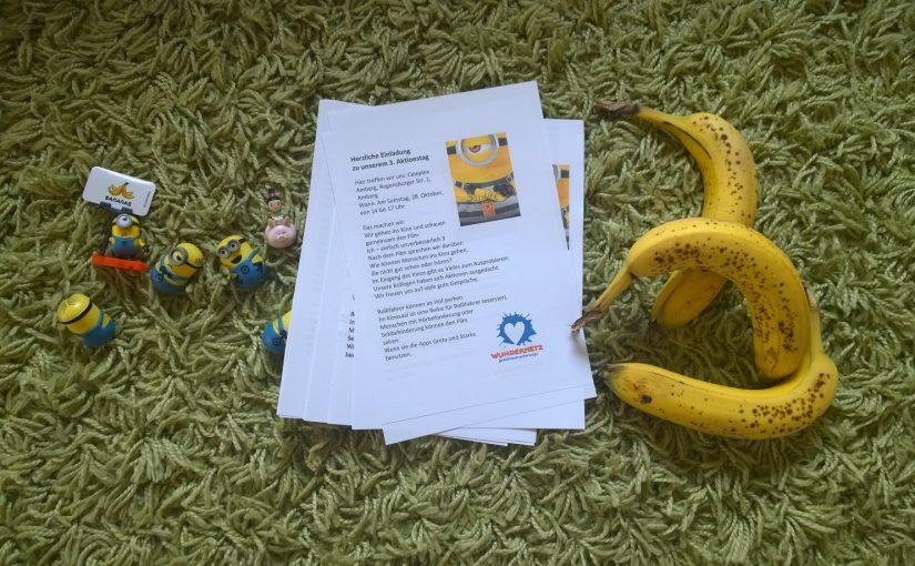 Einladungsflyer für den Kinotag liegen auf einem Teppich. Daneben sind kleine Minions-Figuren und drei Bananen.