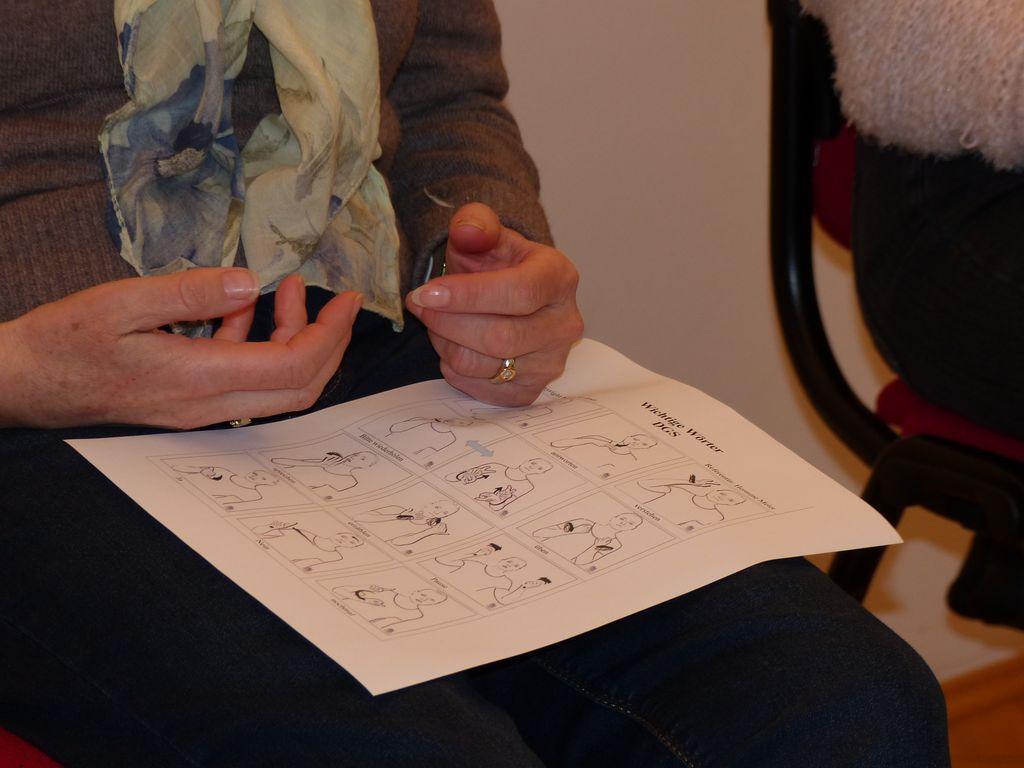 Zwei Hände liegen auf einem Blatt. Das Blatt zeigt die Zeichen für das Fingeralphabet.