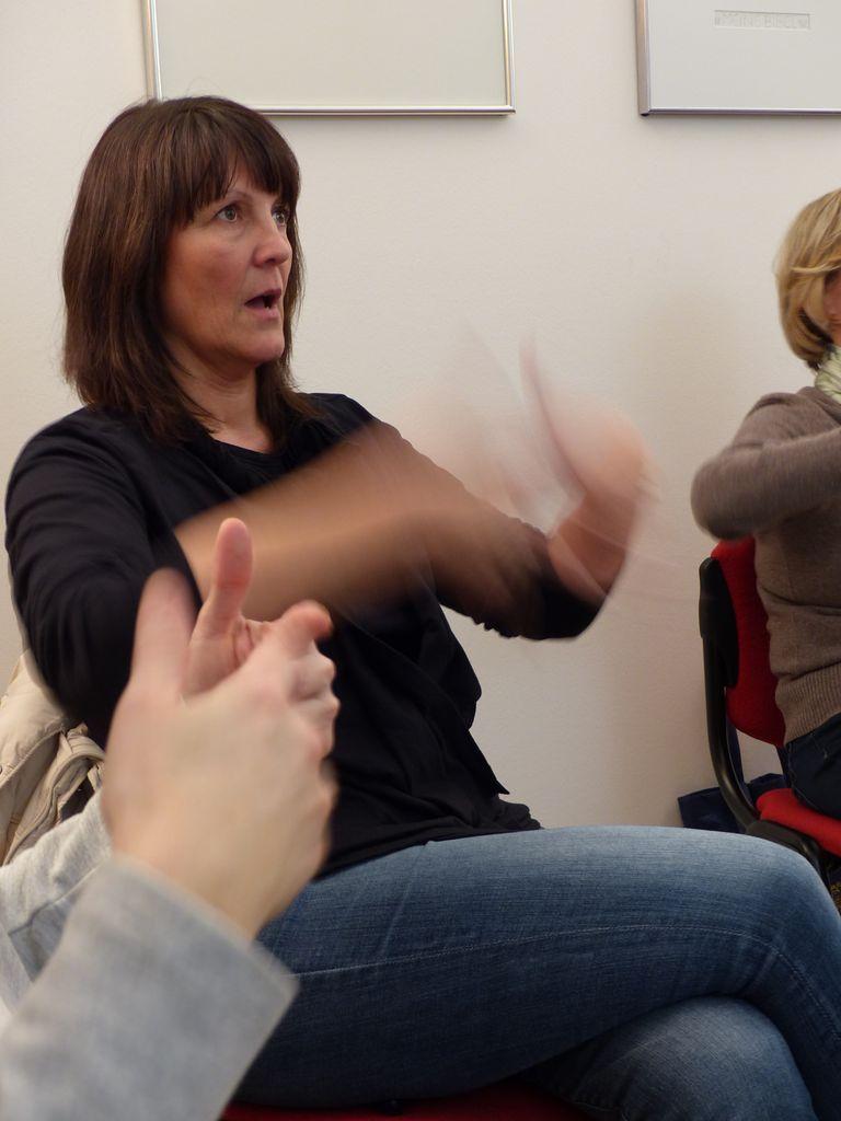 Kursteilnehmerin Geli übt die Handzeichen und das lautlose Aussprechen des Begriffs.