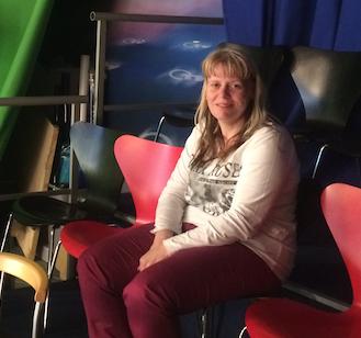 Michaela sitzt auf einem roten Stuhl und lächelt in die Kamera.