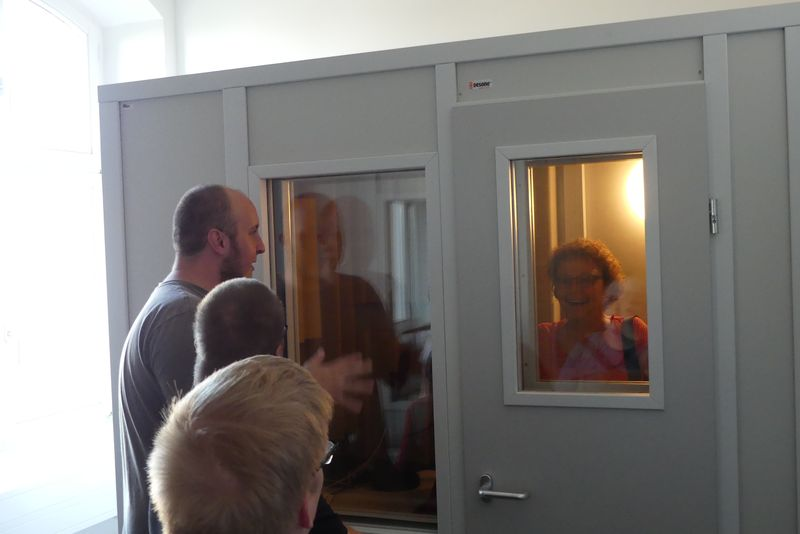 Brigitte ist in der Tonkabine. Bernd und andere Kellegen aus der AG sehen von außen hinein.