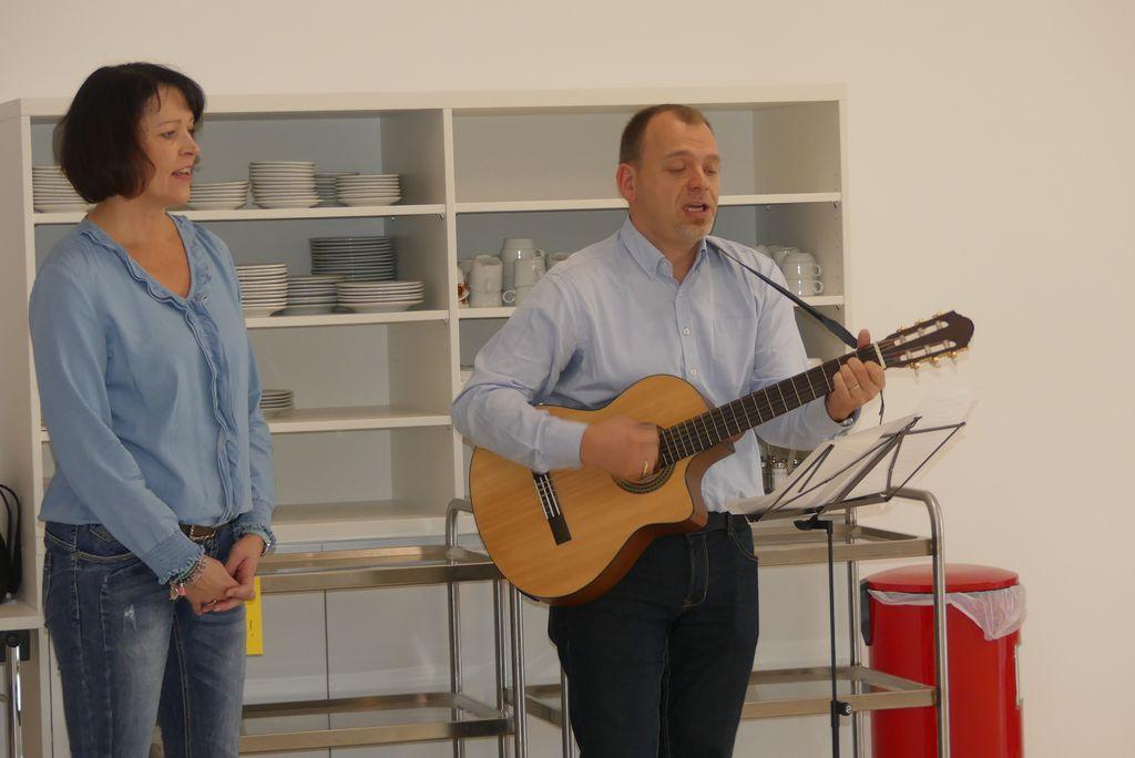"""Sabine steht neben Christian mit der Gitarre. Die beiden singen den """"Wundernetz-Song""""."""