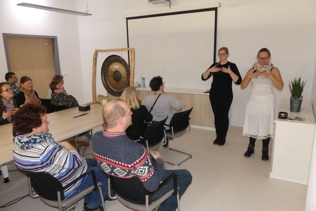 Nadine Schienhammer unterrichtet in Klangmeditation. Links neben ihr steht Kathleen Entrich und übersetzt die Klänge in Gebärdenzeichen.