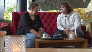 Silvia und Simone sitzen auf einem gemütlichen roten Sofa in einem Cafe bei den Dreharbeiten.