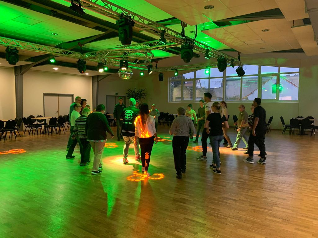 Die Tänzer stehen im Kreis und werden gründ und orange beleuchtet.