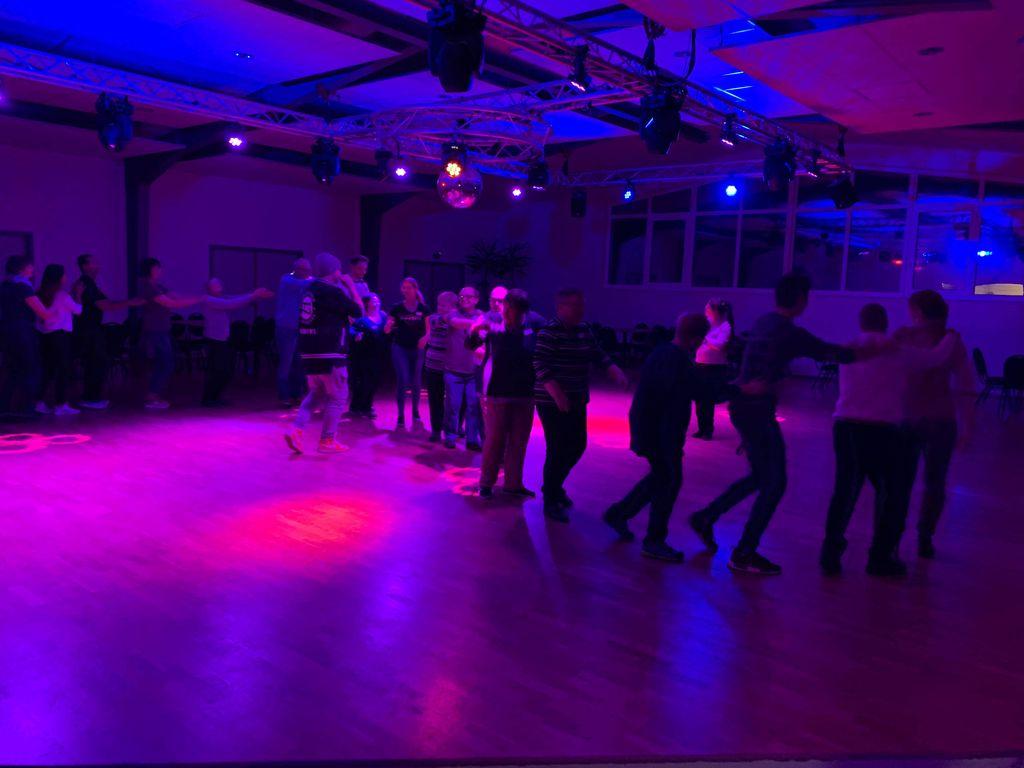 Polonaise durch den blaurot beleuchteten Tanzsaal.