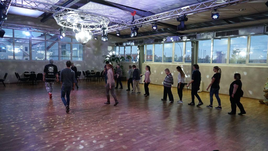 Die Diskokugel wirft silberne Lichtpunkte über den Saal. Dort wird gerade eine Choreografie geübt.