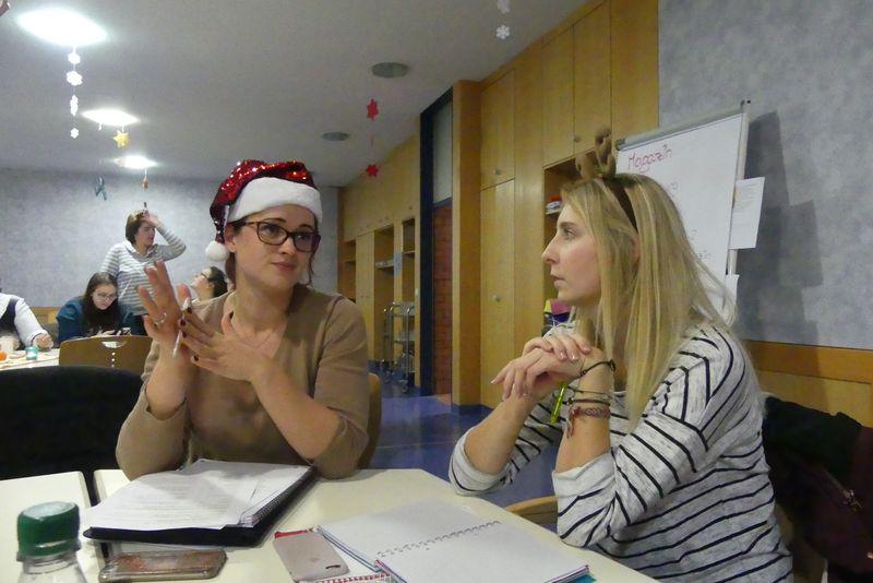 Julia trägt eine rote Glitzernikolausmütze und plaudert mit Lisa mit Rentiergeweih.