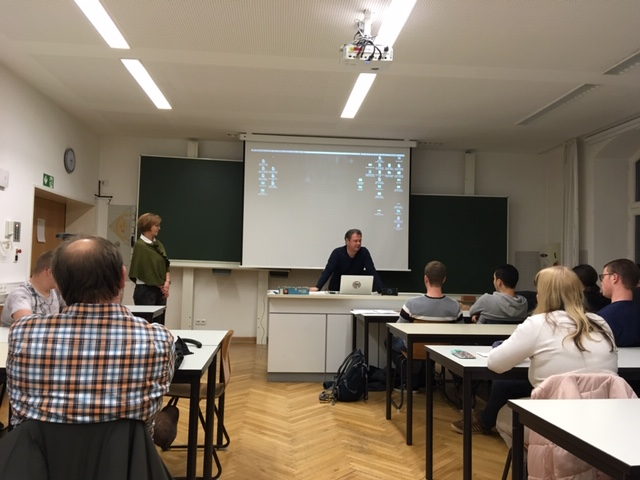 Professor Müller steht vorne am Pult und spricht mit der Arbeitsgruppe, neben ihm Hildegard Legat.