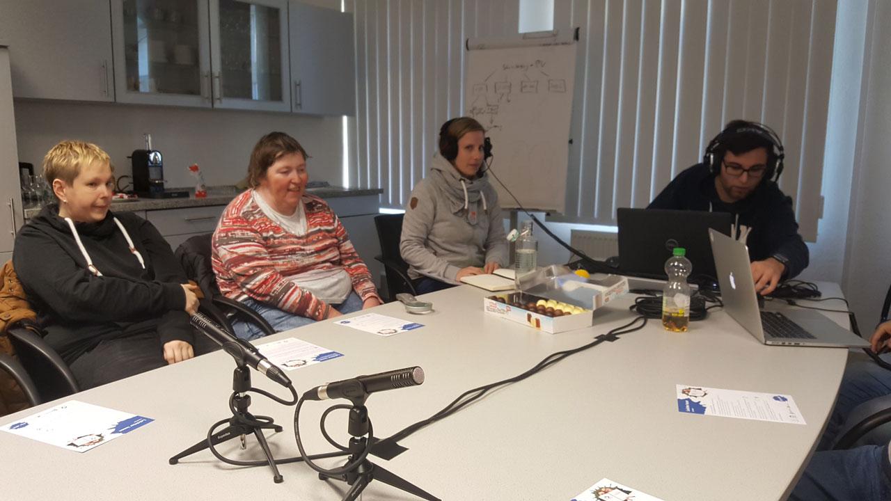 Die Teilnehmer am Podcast sitzen vor Mikrofonen, die auf dem Tisch positioniert sind.